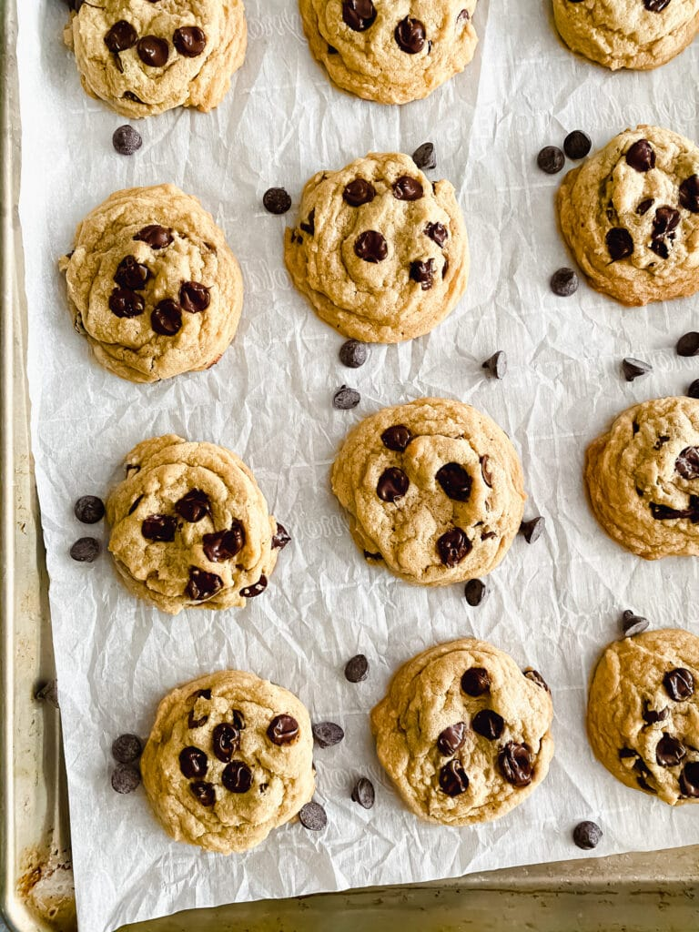 chocolate chip cookies on sheet pan with parchment paper and chocolate chips