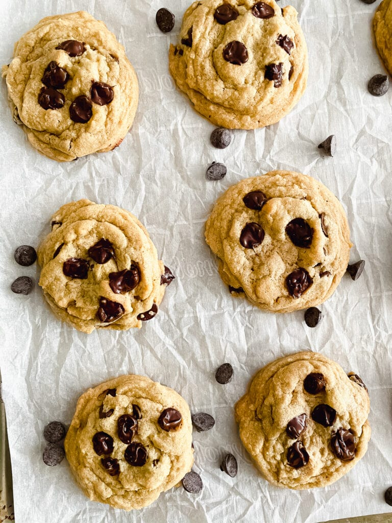 chocolate chip cookies on sheet pan with parchment paper with chocolate chips