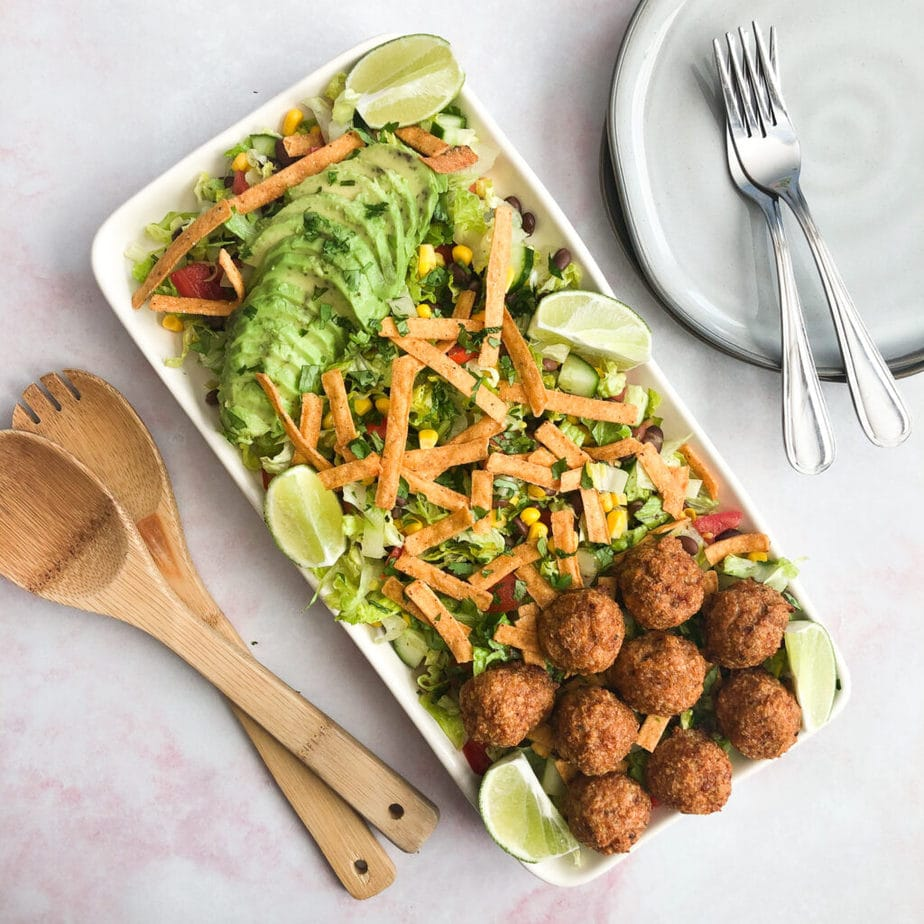 Mexican chopped salad topped with meatballs on white platter with wooden serving spoons