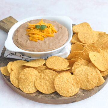 spicy bean dip topped with shredded cheese and cilantro in white dish on serving board with tortilla chips