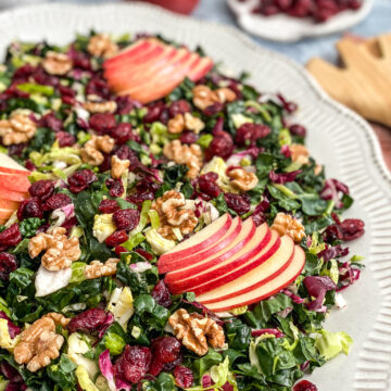 close up shot of harvest chopped salad topped with thinly sliced red apples
