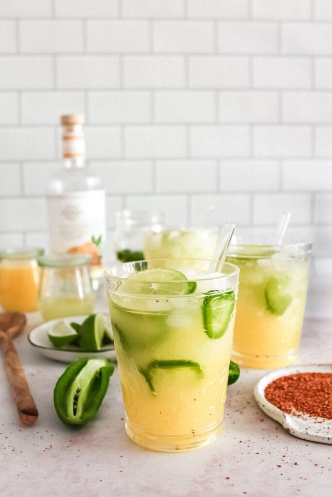 spicy margaritas over ice with garnishes spread around the table