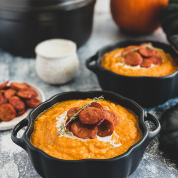 squash soup topped with sliced sausage and drizzled with cream served in black ceramic pumpkins