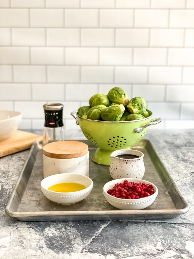 sheet tray of recipe ingredients featuring Brussels sprouts, salt, pepper, olive oil, pomegranate seeds and balsamic glaze
