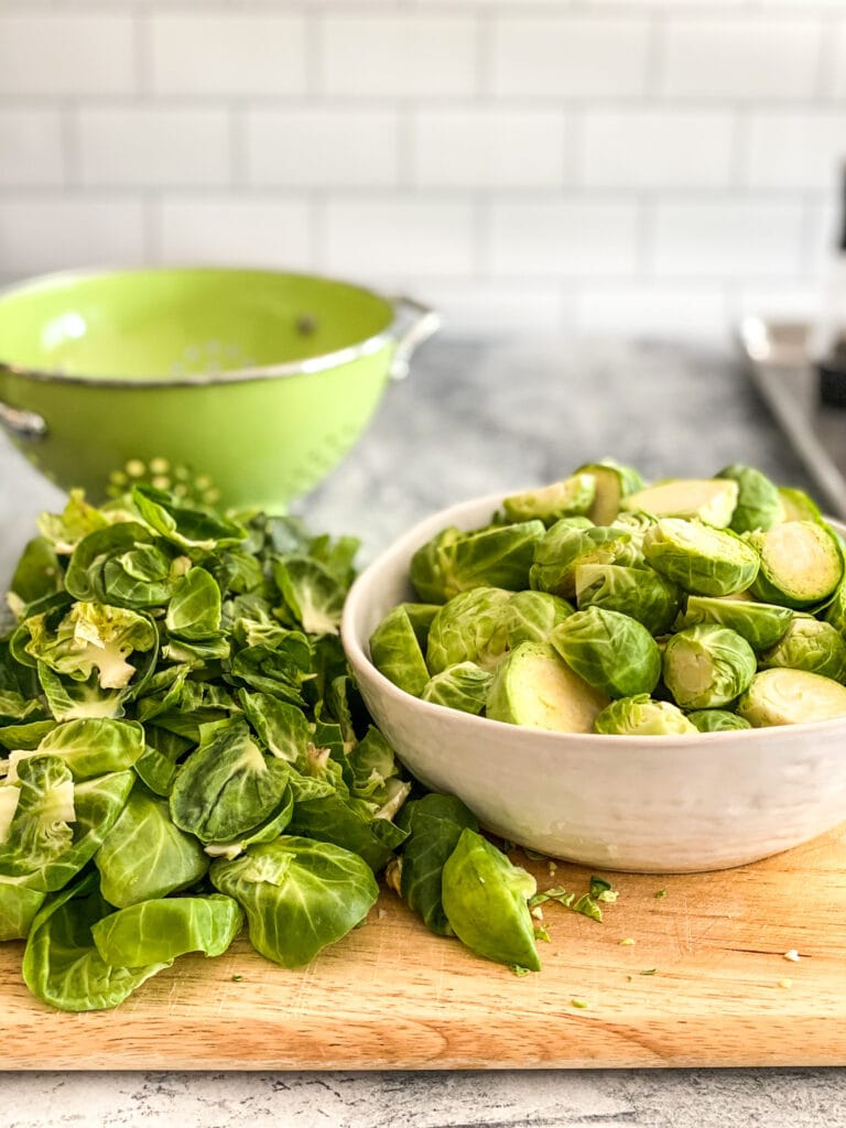 sliced raw brussels sporuts in a white bowl next to a pile of Brussels sprouts leaves that were trimmed off