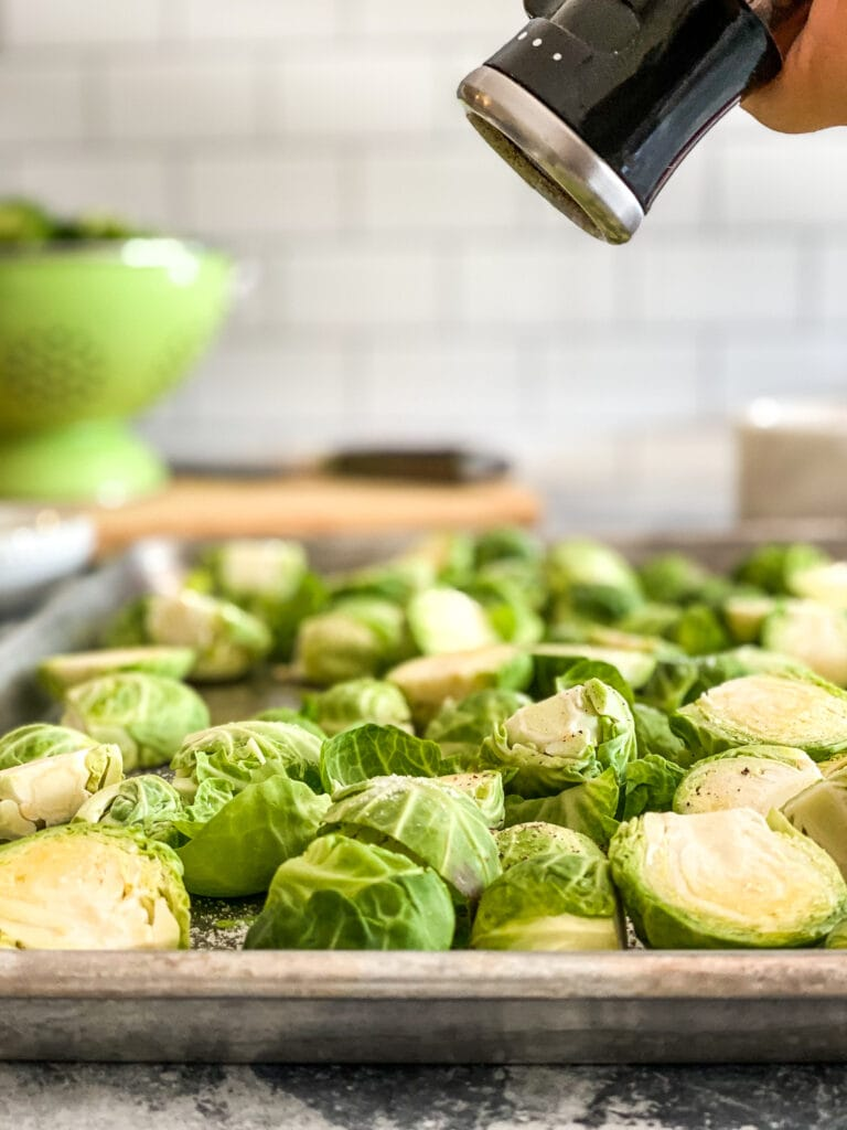 sheet pan with raw Brussels sprouts being seasoned with a pepper mill from above