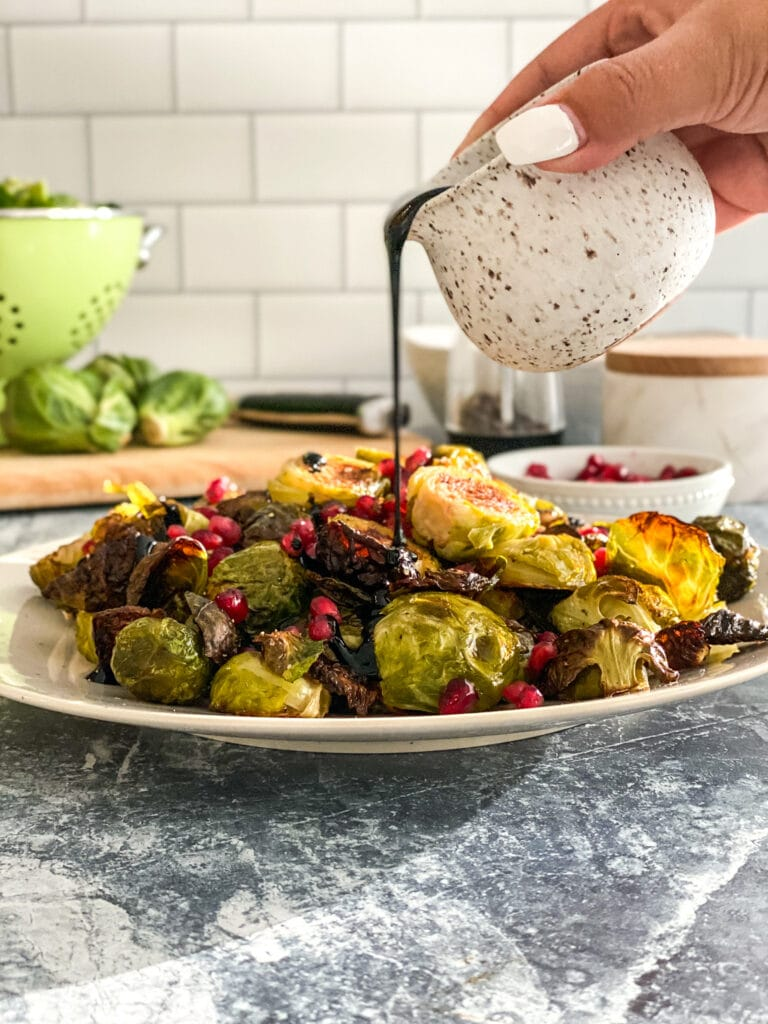 white plate with roasted Brussels spouts and pomegranate seeds being drizzled with balsamic glaze from above