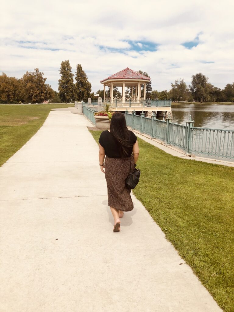 photo of me taken from the back, walking through Denver city park by the water