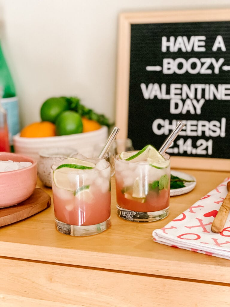 grapefruit and mint fizz in rocks glass with crushed ice and lime wedges