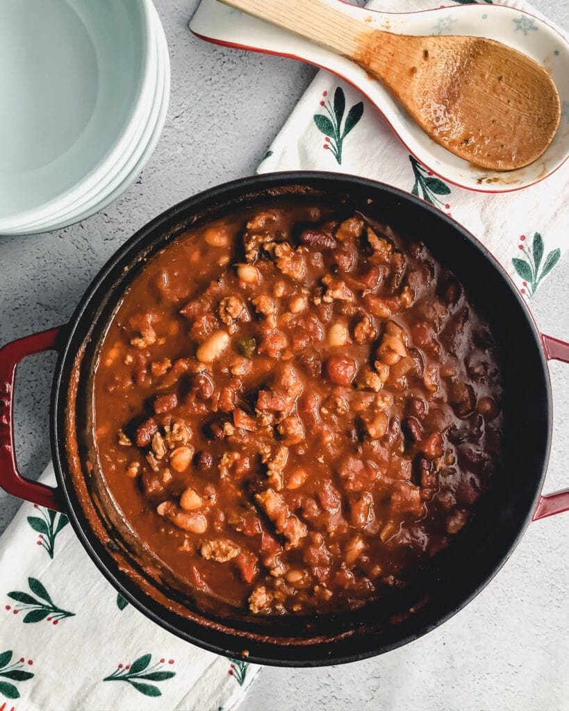 dutch oven filled with chili next to a set of serving bowls and a wooden serving spoon