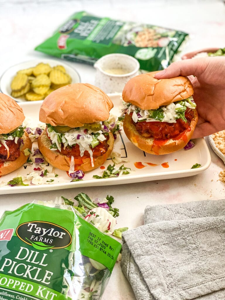 dill pickle buffalo chicken sandwiches assembled on a serving platter with salad bag in the corner
