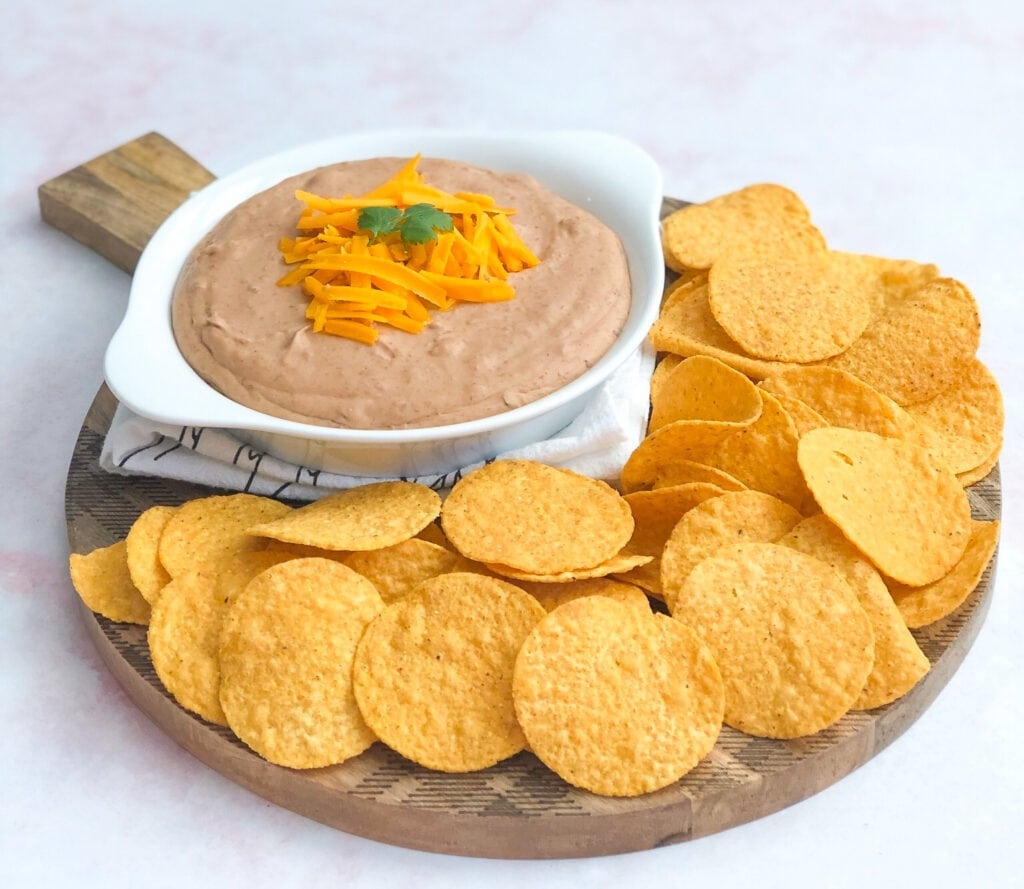 spicy bean dip in white ceramic serving dish garnished with cheddar cheese and cilantro served with tortilla chips