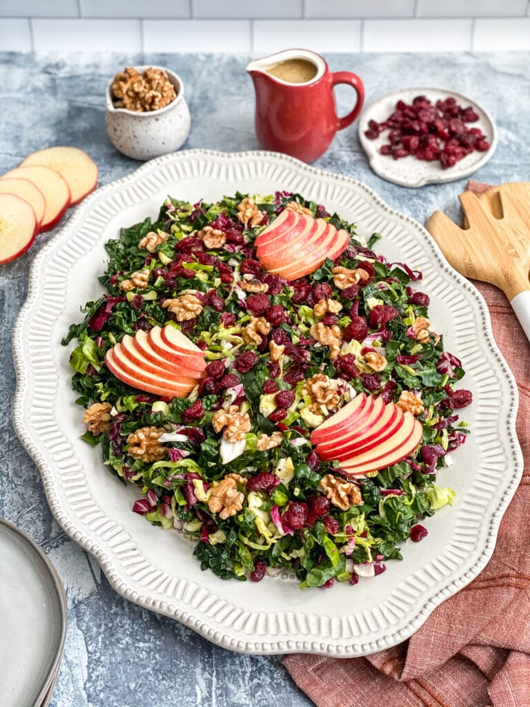 salad with apples on top and dressing in the background on large white platter