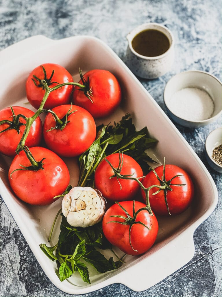 baking dish with tomatoes, basil and garlic ready to be roasted in the oven