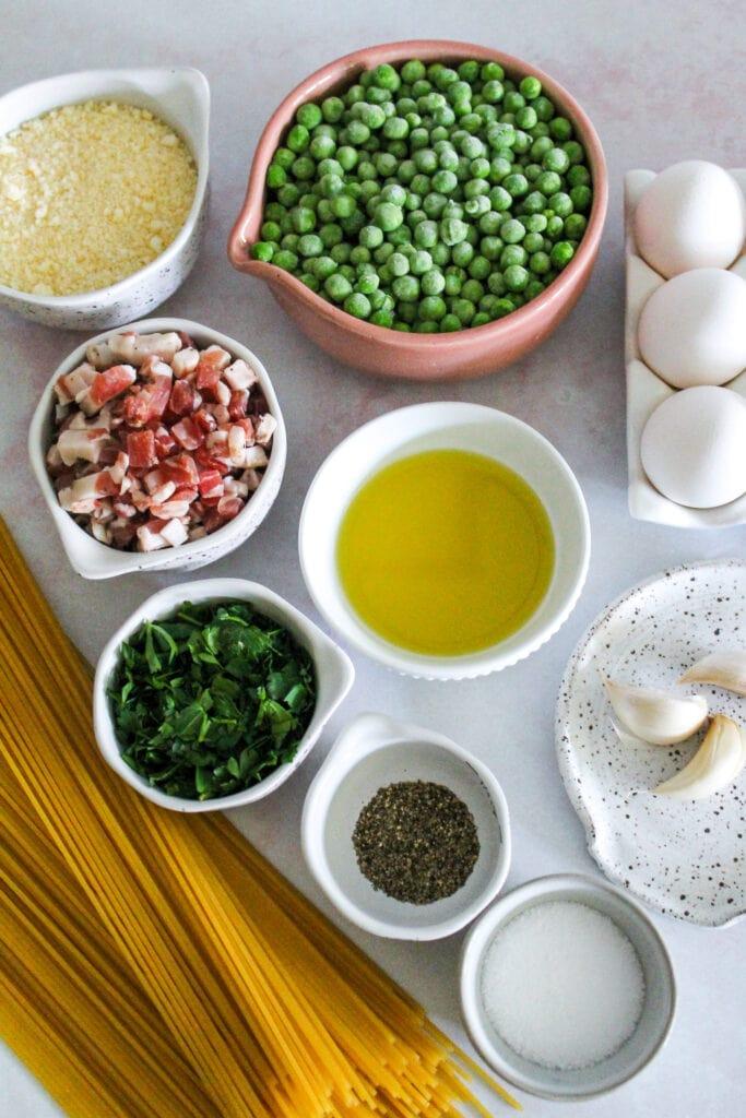 ingredients to make spaghetti carbonara measured out: pasta, pancetta, peas, eggs, cheese, garlic, salt and pepper