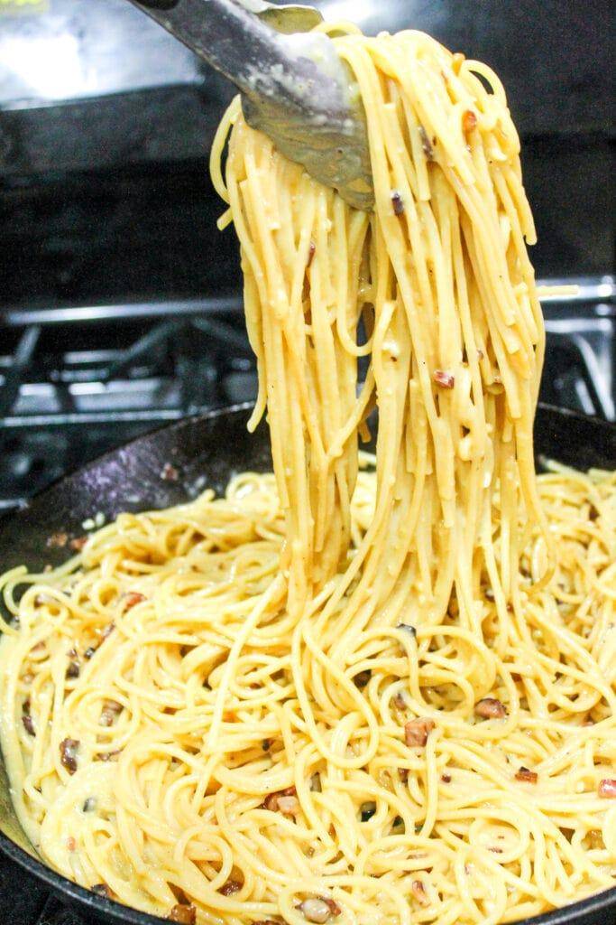 spaghetti carbonara in the pan before adding peas
