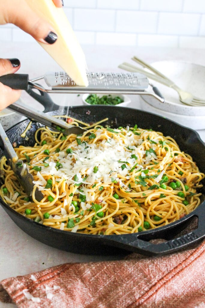 spaghetti carbonara in serving dish topped with parsley and parmesan cheese