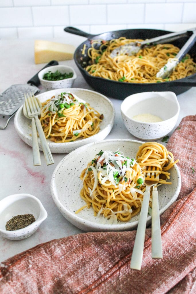 spaghetti carbonara plated, topped with parsley and parmesan cheese