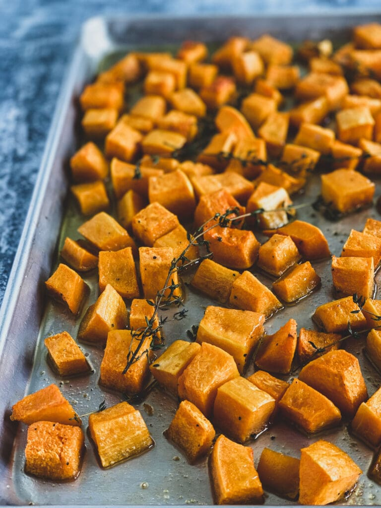 roasted squash on a sheet pan with sprigs of thyme on top