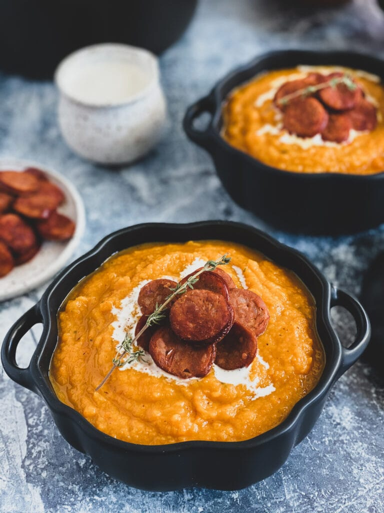 butternut squash soup with linguica and thyme served with cream in a ceramic pumpkin