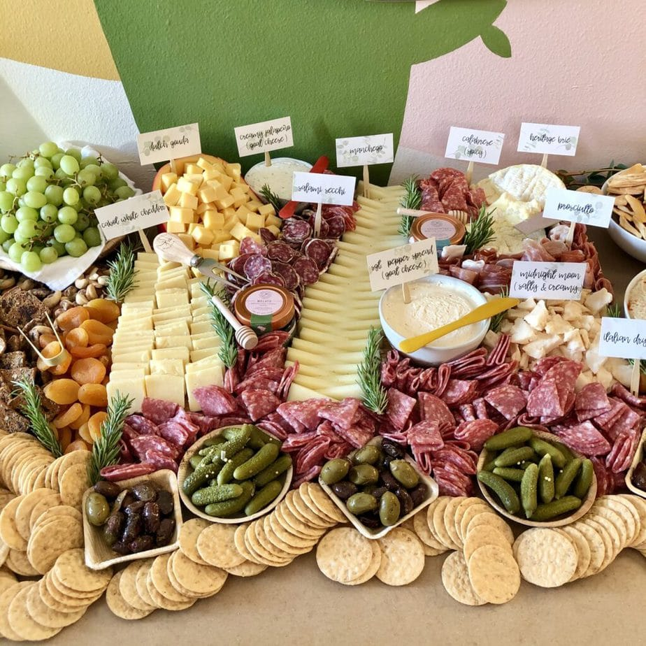 meat and cheese on a large table for a party