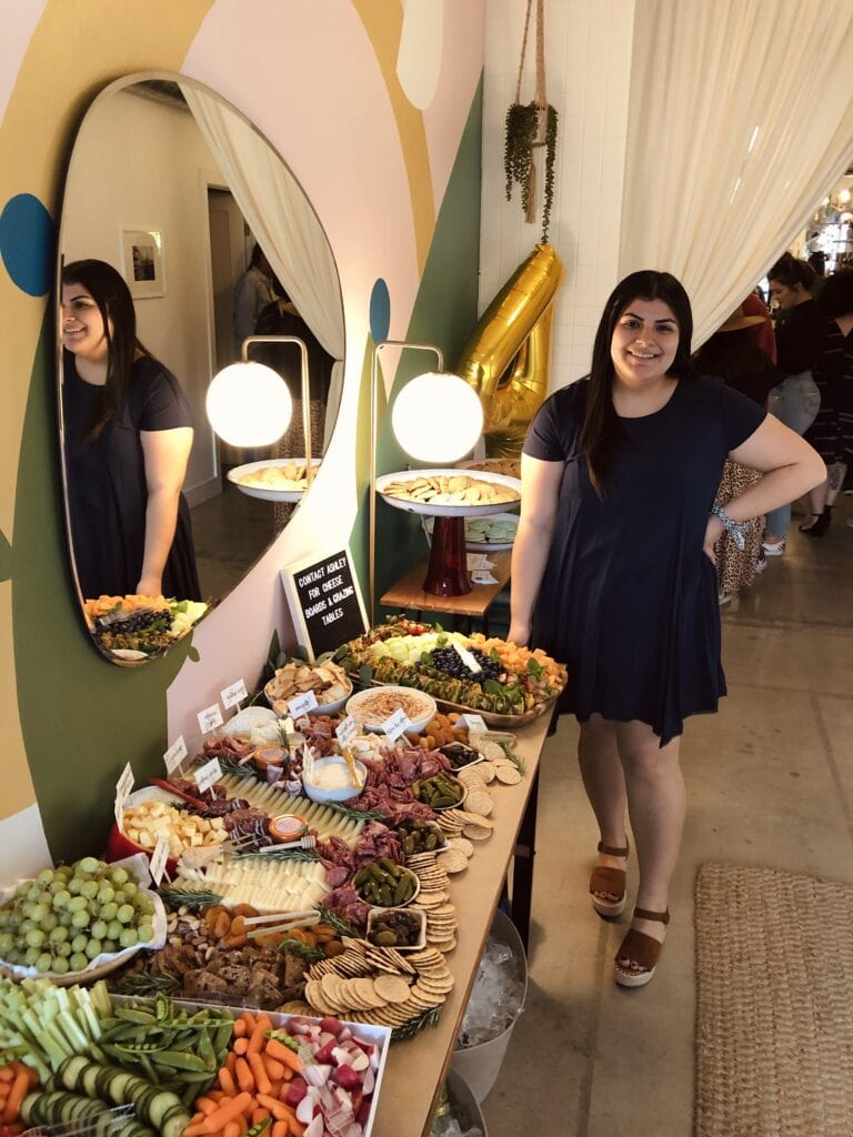 me standing in front of a grazing table filled with meat cheese veggies and fruit