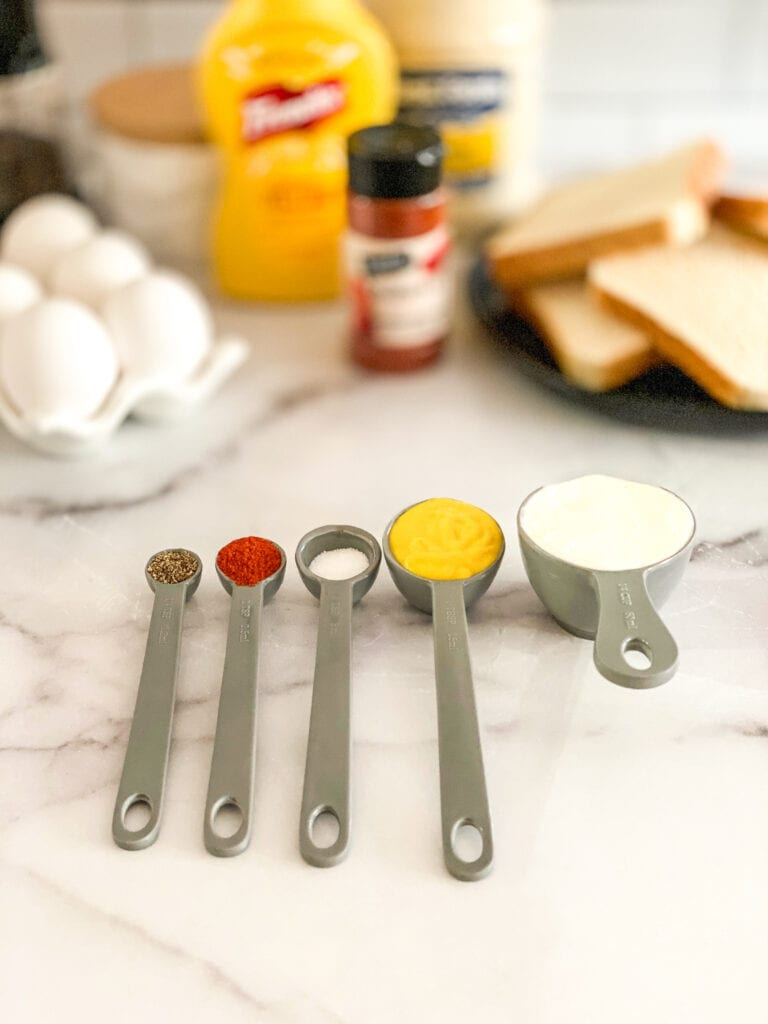 classic egg salad ingredients measured out in measuring spoons and cups
