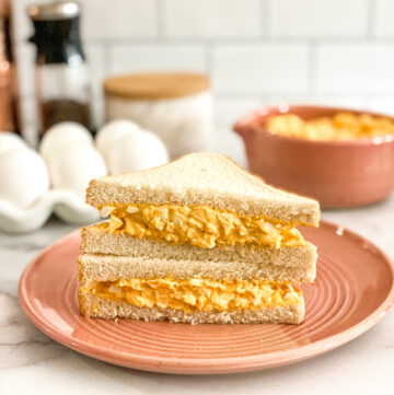 egg salad sandwich on white bread served on pink plate
