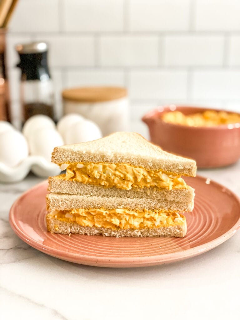 egg salad sandwich on white bread served on a pink plate