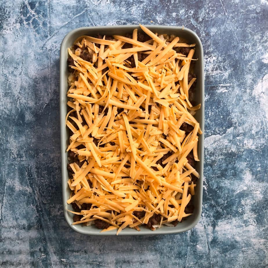 cheesy sausage and hash browns casserole before being baked in the oven, in a green casserole dish