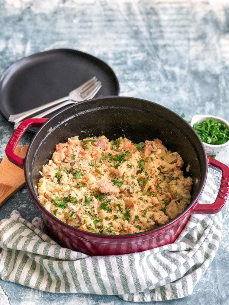 parmesan chicken and rice in red Dutch Oven with parsley on top