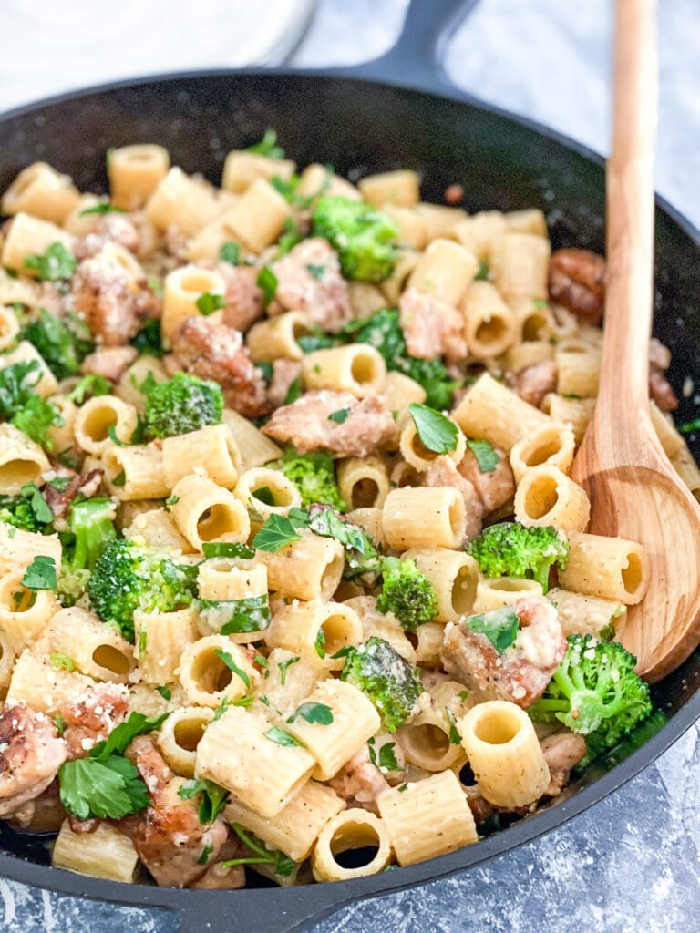 creamy chicken pasta in cast iron skillet with wooden serving spoon