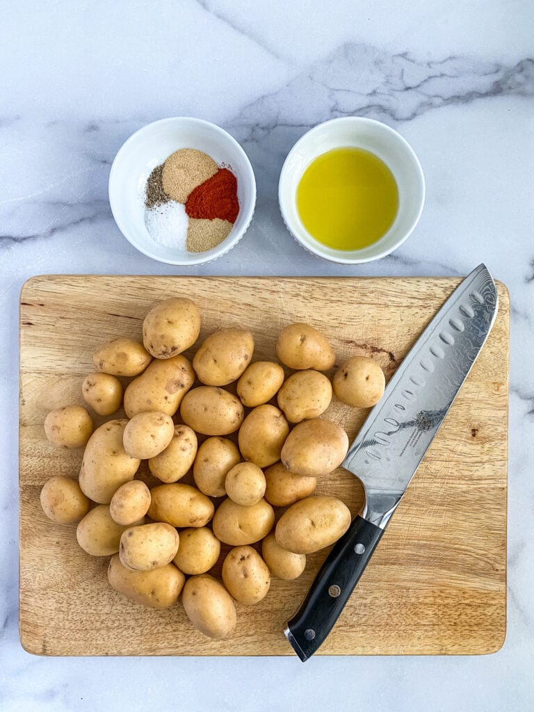 whole potatoes on a cutting board with a knife. above the cutting board are dishes of the seasoning mixture and olive oil