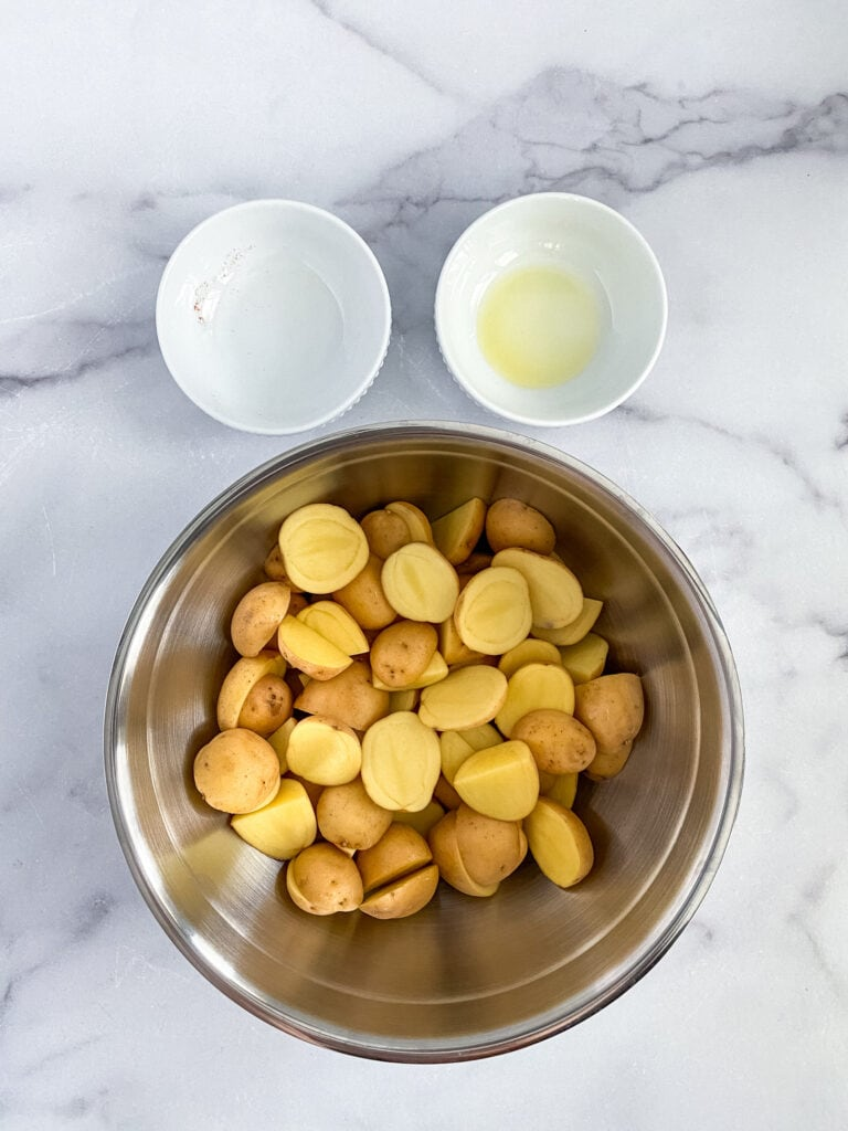 cut potatoes sitting on top of the seasoning mixture and olive oil in the bowl