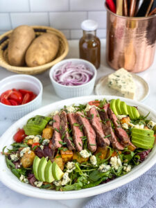 steak salad dressed on a serving platter with extra ingredients in the background