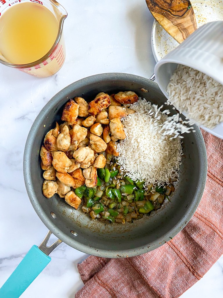 cooked vegetables with seasoning mixture in sauté pan, with tequila added to deglaze. chicken & broth have been added back to the pot