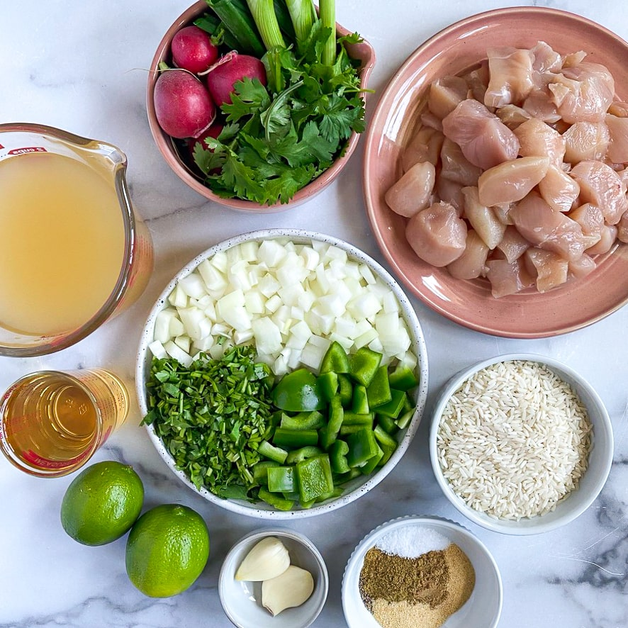 ingredient shot for tequila lime chicken and rice. all ingredients are measured out & in small bowls. ingredients are: chicken, vegetables, rice, seasonings, garlic, lime, tequila, broth and radish salsa ingredients