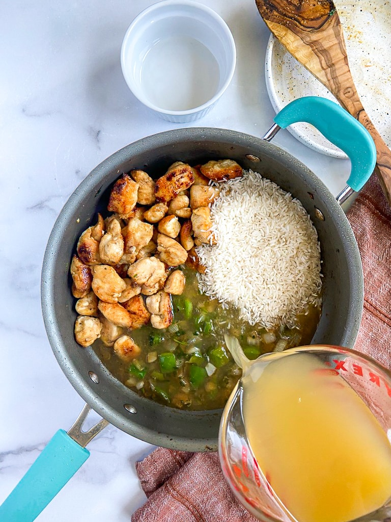 cooked vegetables with seasoning mixture in sauté pan, with tequila added to deglaze. chicken, rice & broth have been added to the pot