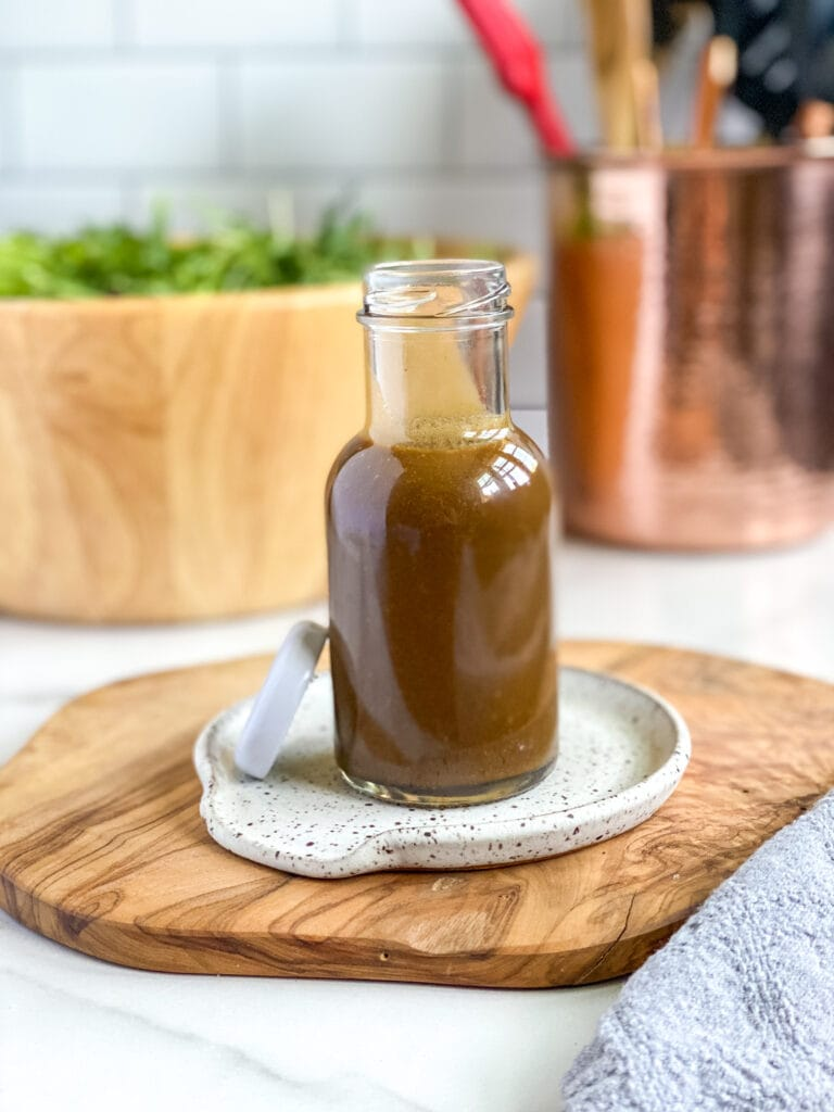 creamy balsamic dijon dressing in small glass jar for serving with bowl of salad in the background