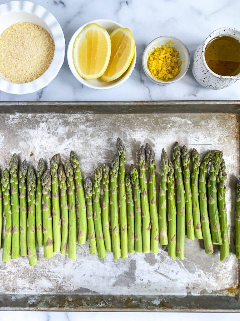 unseasoned asparagus on a sheet pan