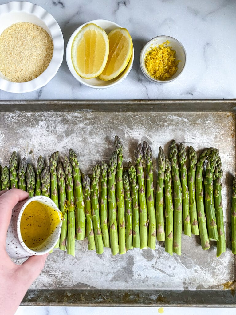 asparagus on a sheet pan being drizzled with olive oil