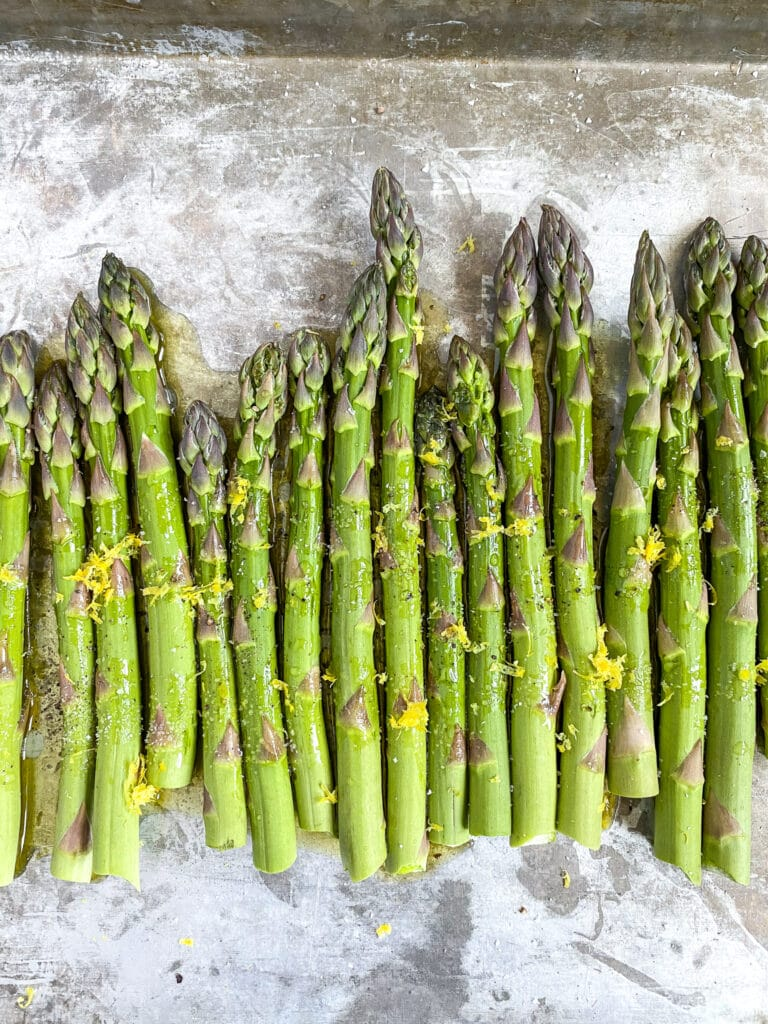 close up shot of roasted parmesan asparagus with all of the seasoning mixed in