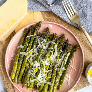 lemon parmesan asparagus on a pink ceramic plate resting on a wooden cutting board with a fork in the background & a wedge of Parmesan Cheese