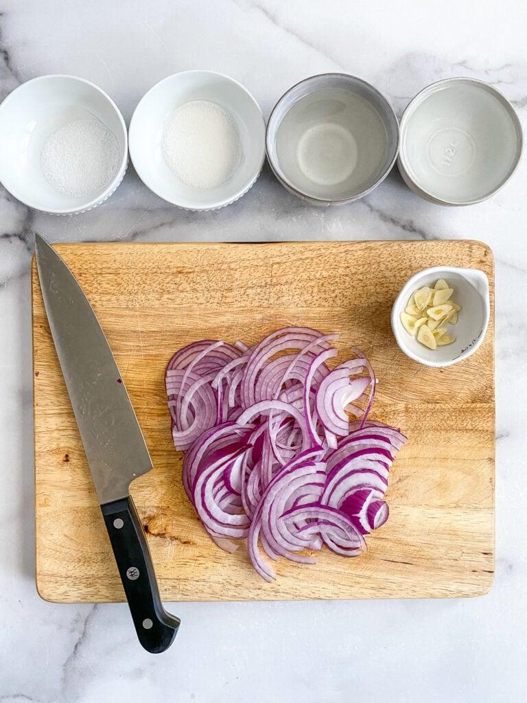 ingredients for quick pickled onions: sliced onions & garlic, vinegar, water, salt & sugar.