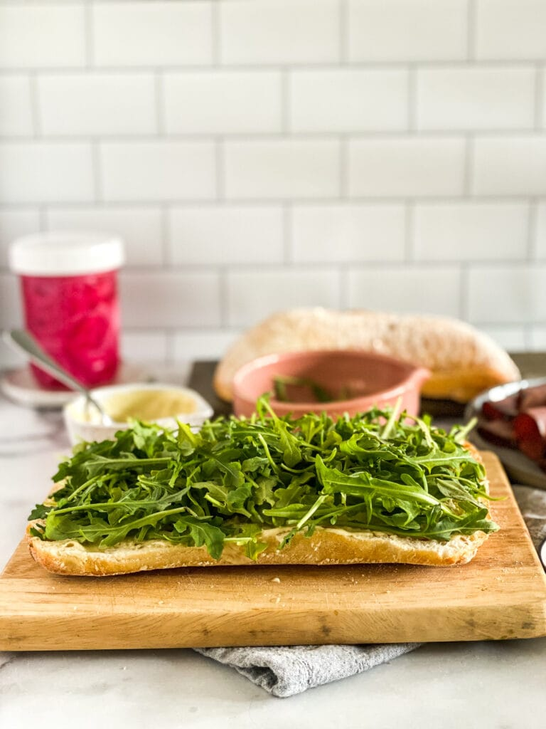 ciabatta loaf with horseradish cream sauce slathered on the bread and topped with arugula.