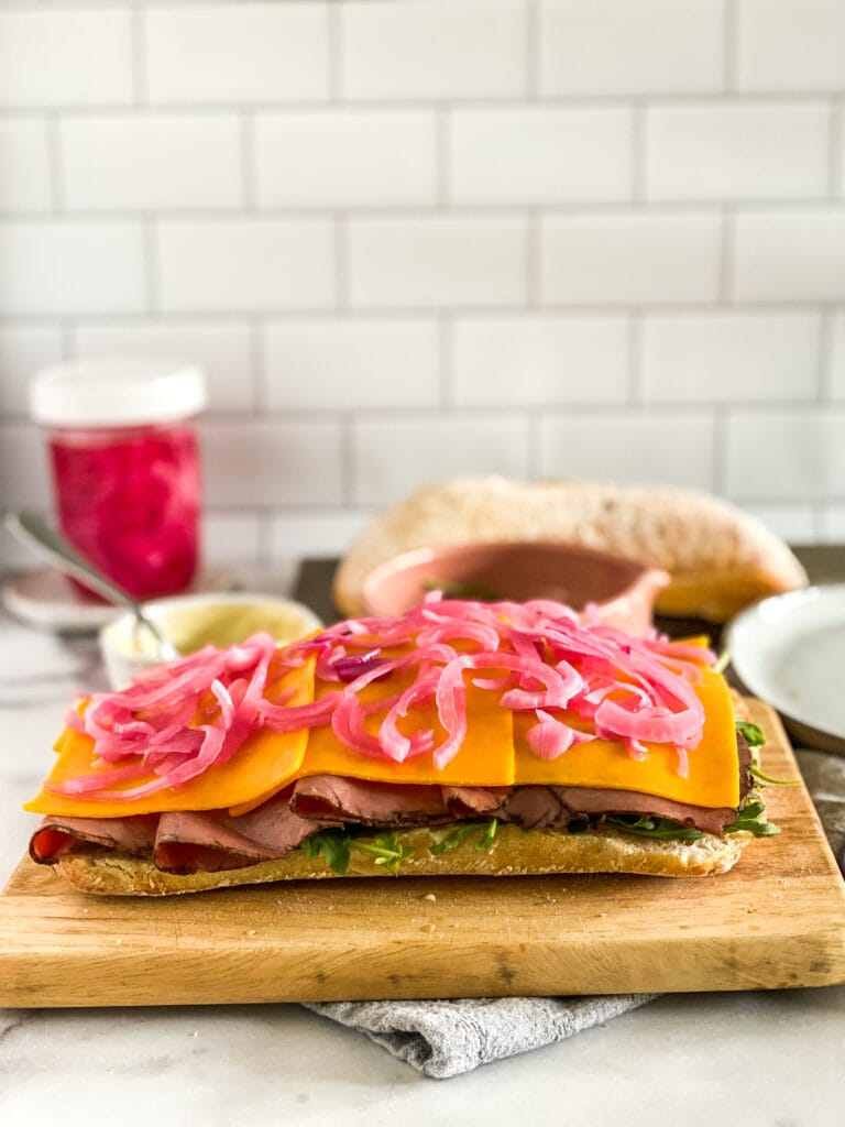 ciabatta loaf with horseradish cream sauce slathered on the bread and topped with arugula,roast beef, cheddar cheese, and quick pickled onions.