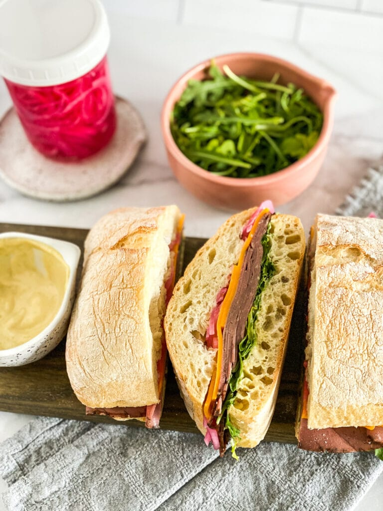 roast beef sandwiches, sliced and wrapped in newspaper. Sandwiches are stacked up on a cutting board with leftover ingredients in the background.